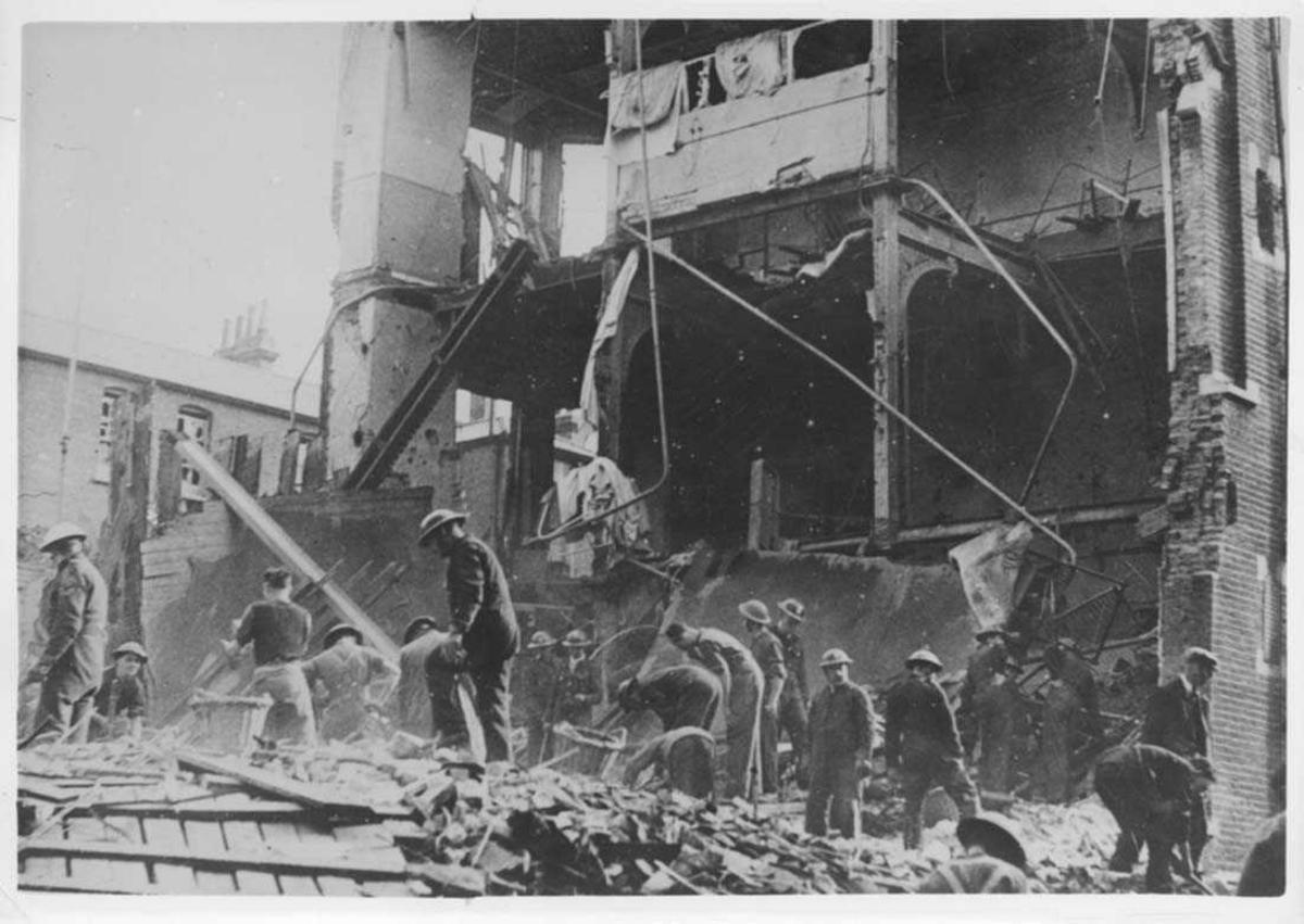En bygning som som er ødelagt etter bombing. Flere personer som holder på å rydde opp.