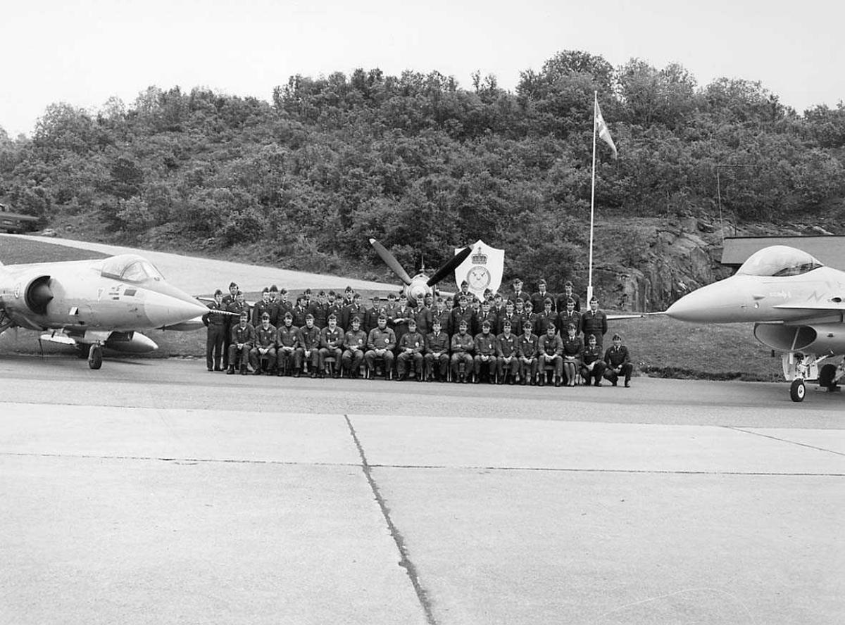 Gruppefoto hvor personellet er plassert mellom 2 jagerfly samt ett i bakkant.