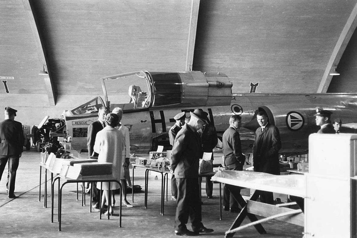 Personer som iakttar jagerfly som er på utstilling.