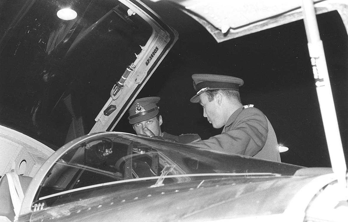 Kronprinsen og en militær offiser. I forgrunnen et fly.