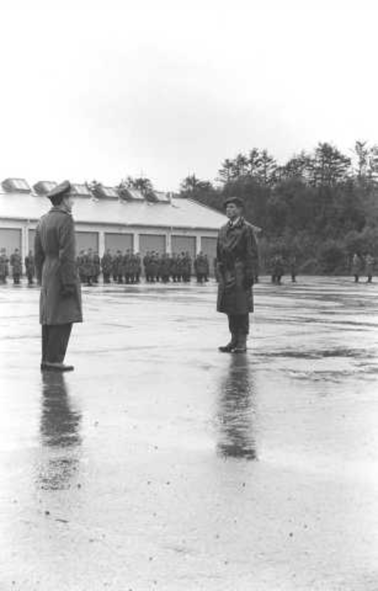 Soldater, befal og offiserer på oppstilling. 1 bygning samt skogsbevokst område i bakgrunnen.
