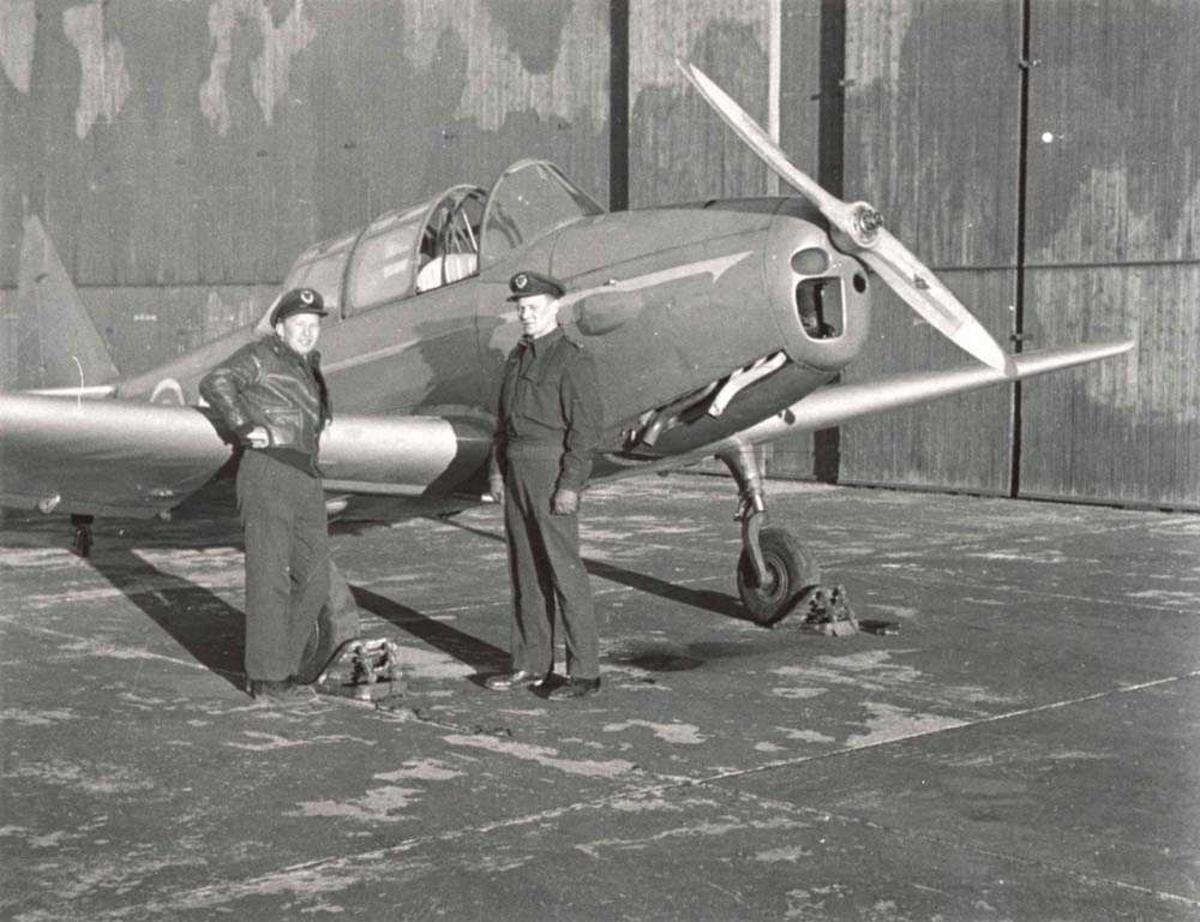 1 fly på bakken. Fairchild Cornell. 2 personer står ved flyet. Hangar i bakgrunnen.