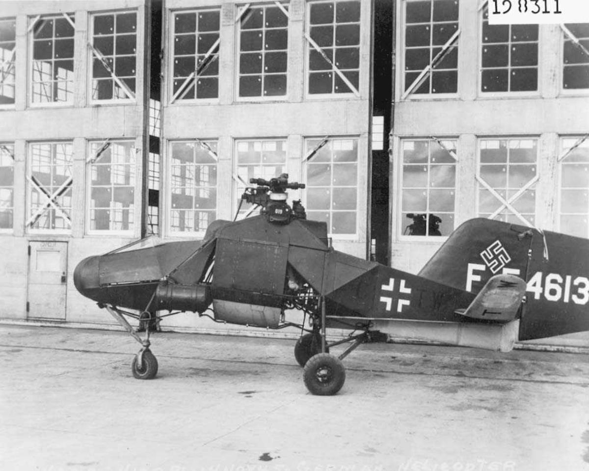 1 helikopter på bakken. Flettner Fl 282 Kolibri. Står foran en hangar.