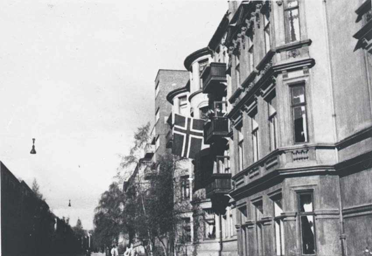 Bygårder. Et norsk flagg henger fra en bygård.