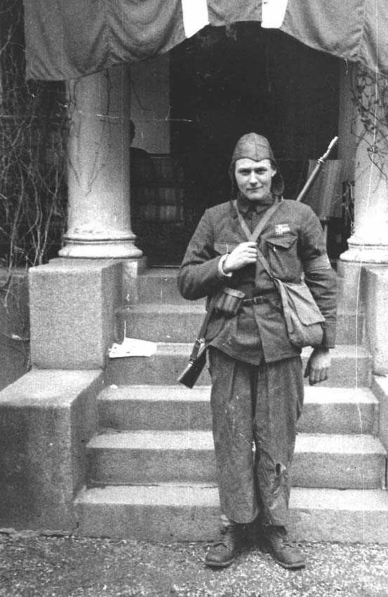 En person. Mann. Står foran en trapp. Har uniform på seg. Har et våpen bak på ryggen.