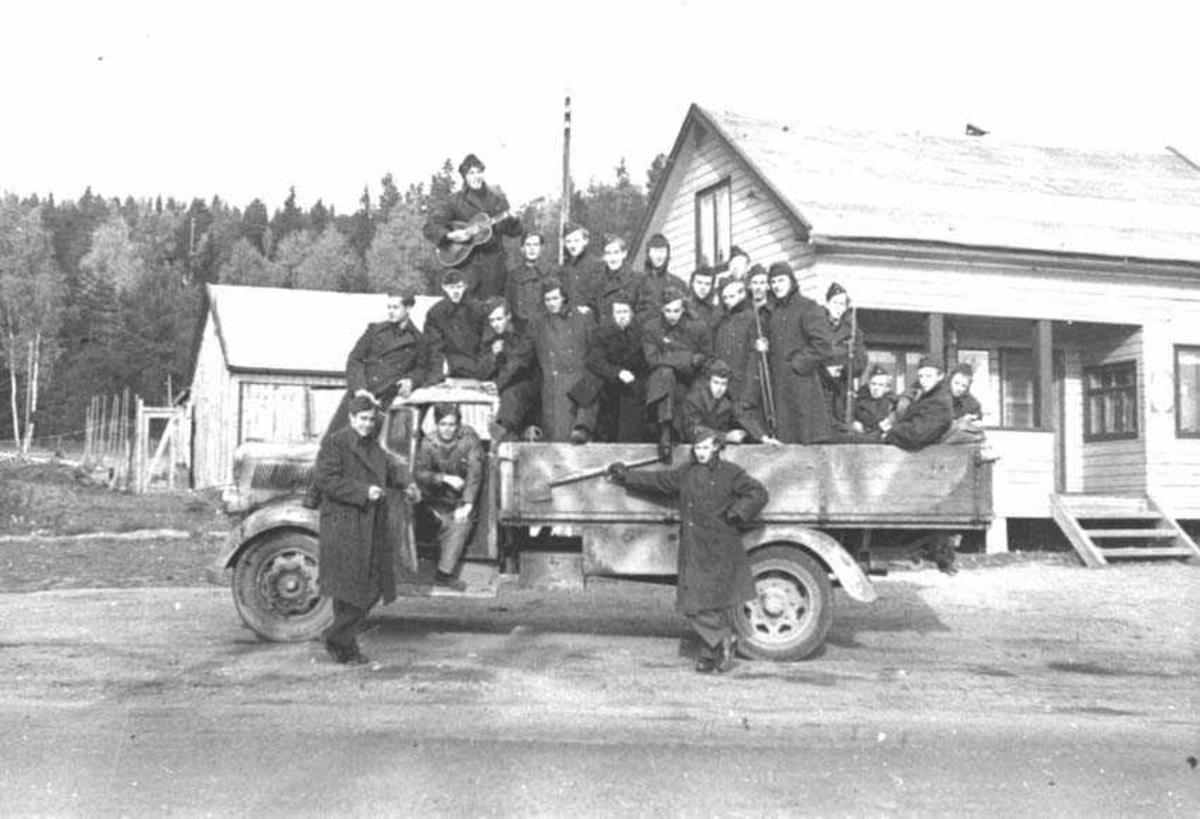 Tropp samlet på og ved en lastebil. En har en gitar i armene. De har på seg militærfrakker. Bygninger i bakgrunnen.