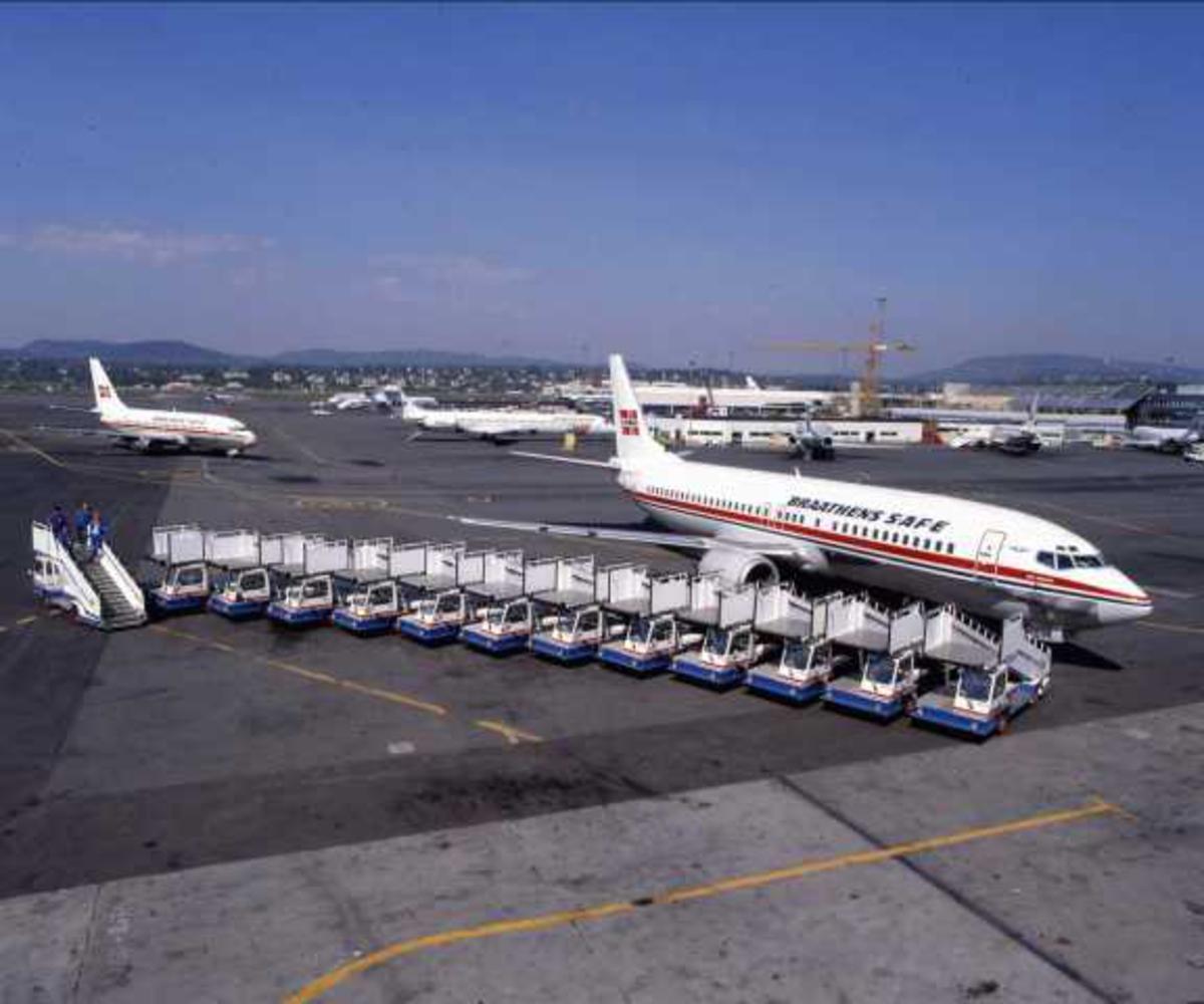Flere fly på bakken. Ett Boeing 737-405 LN-BRB. Tre personer ved flyet.