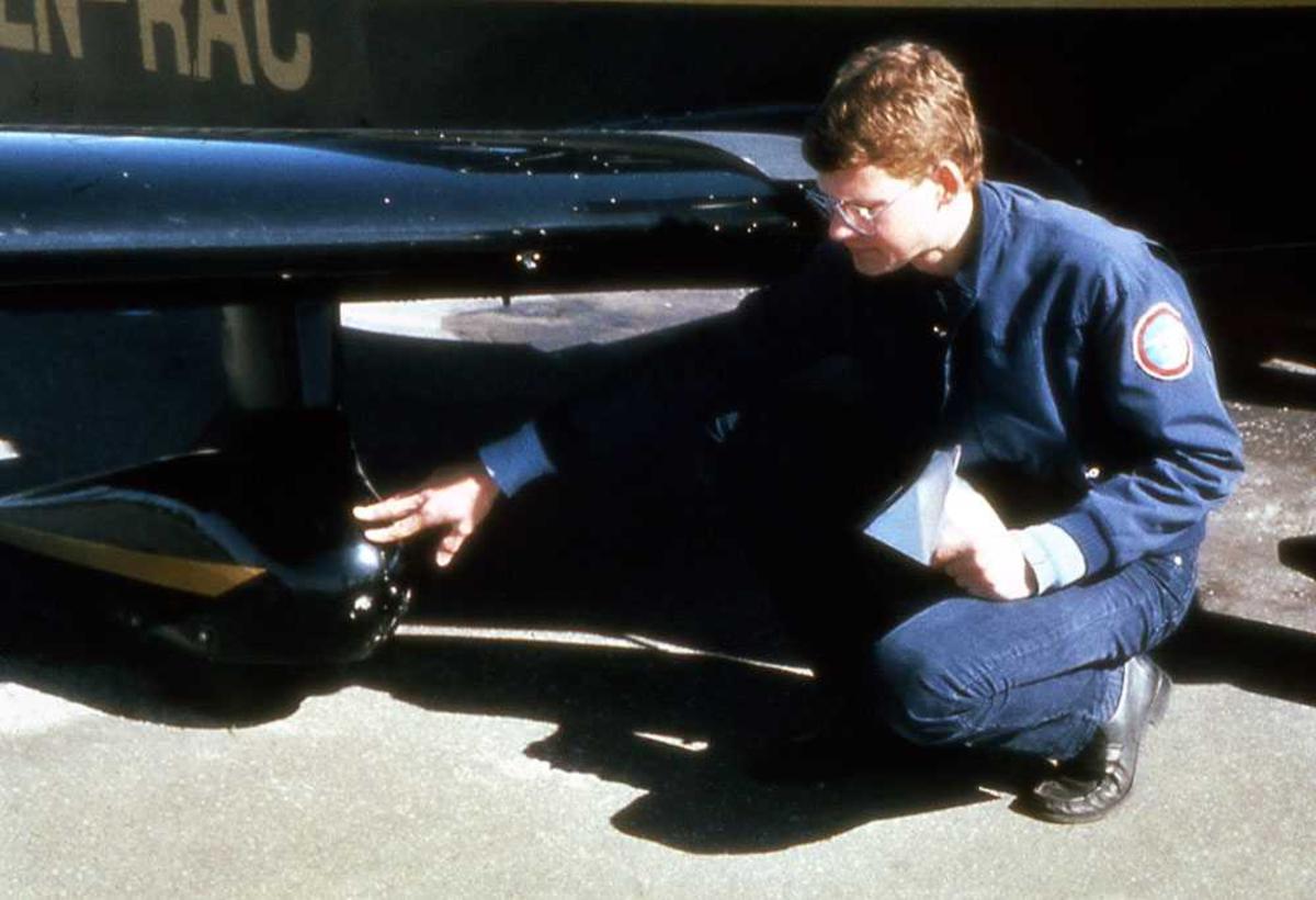 Ett fly på bakken. LN-RAC, Robin R.2160. En person på kne ved flyet. Inspeksjon.