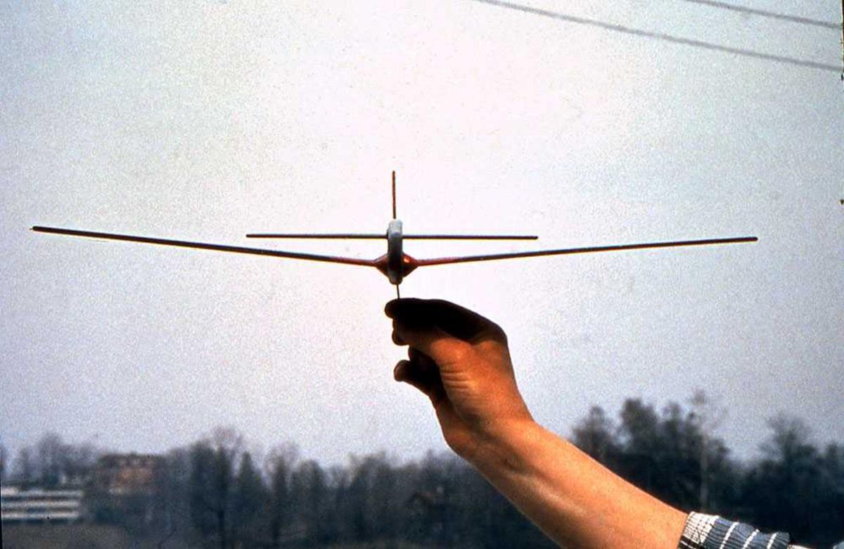 Ett modellfly holdt opp av person. Sett forfra.