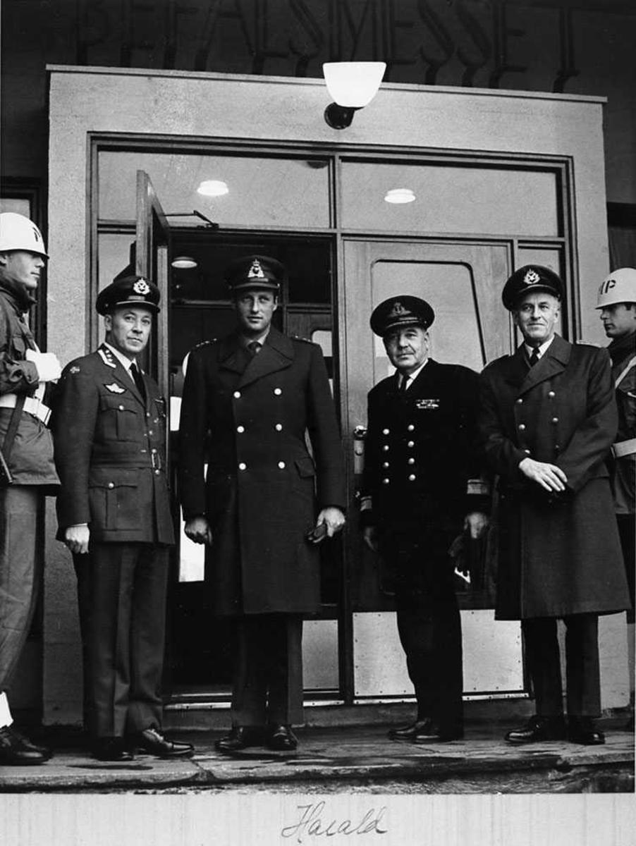 Portrett. Fire personer foran en inngang, menn. To mp-soldater som står vakt ved siden av.