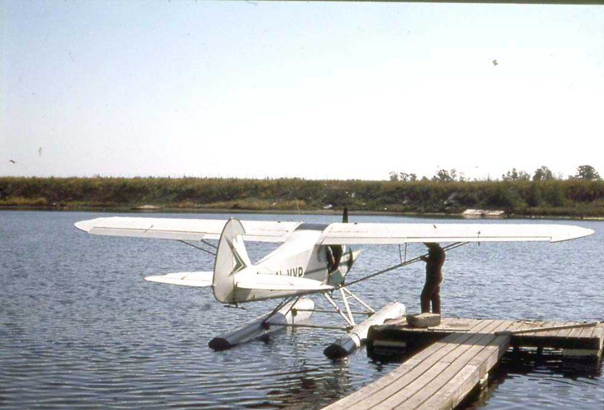 1 sjøfly som ligger til kai. Piper PA-18-150 Super Cub, LN-VYP. En person står på kaien ved flyet.