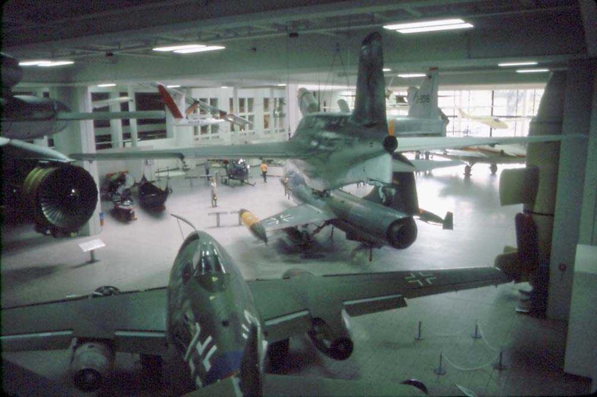 Flere fly innendørs, ant. et museum. Flere personer ved flyene.