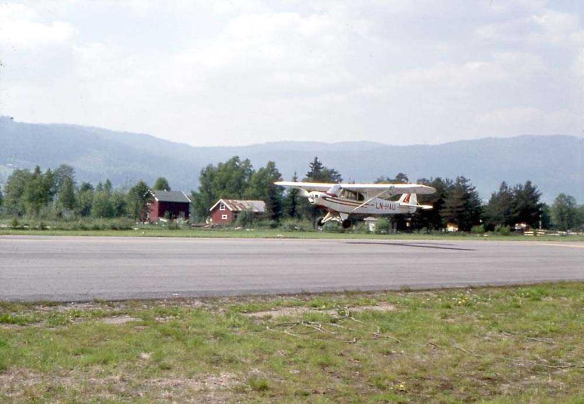 Ett fly like over bakken som tar av/lander, Piper PA-18-150 Super Cub, LN-HAU. Rullebane under flyet. Bygninger og fjell i bakgrunnen.