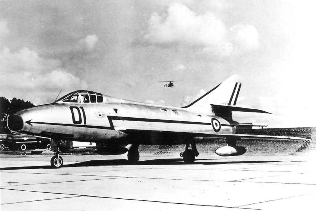 Lufthavn. Ett fly på bakken, Dassault Super-Mystere B2. Ett helikopter i luten i bakgrunnen.