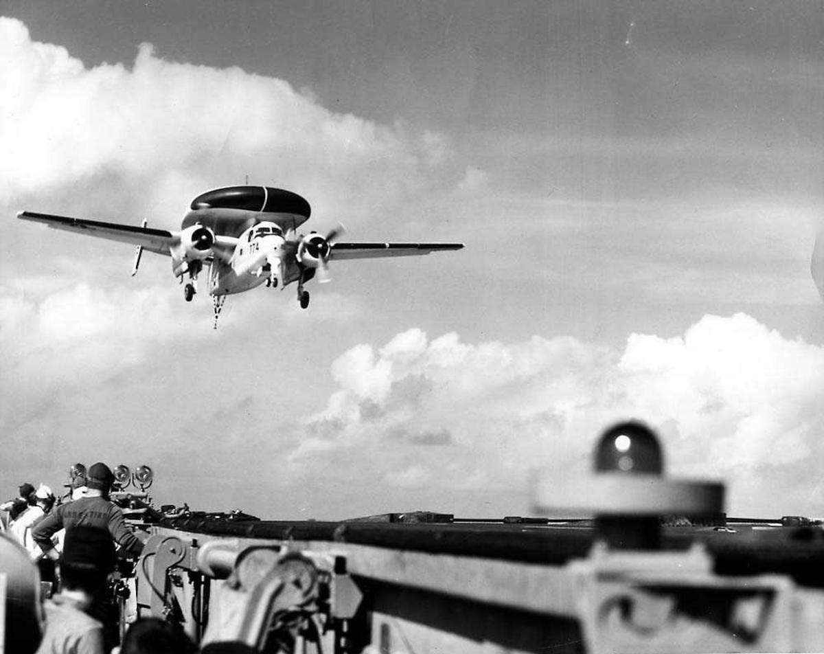 Luftfoto. Ett fly i luften like over dekket til et hangarskjp, Grumman Tracer WF-2.