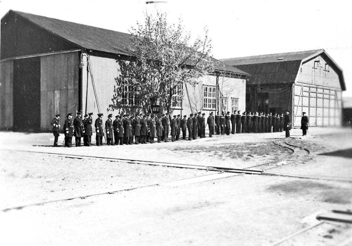 Militærtropp som står oppstilt foran en bygning.