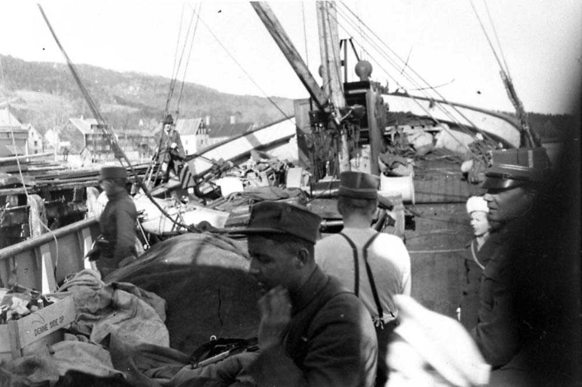 Flere personer ombord i en båt. Bygninger og fjell i bakgrunnen.
