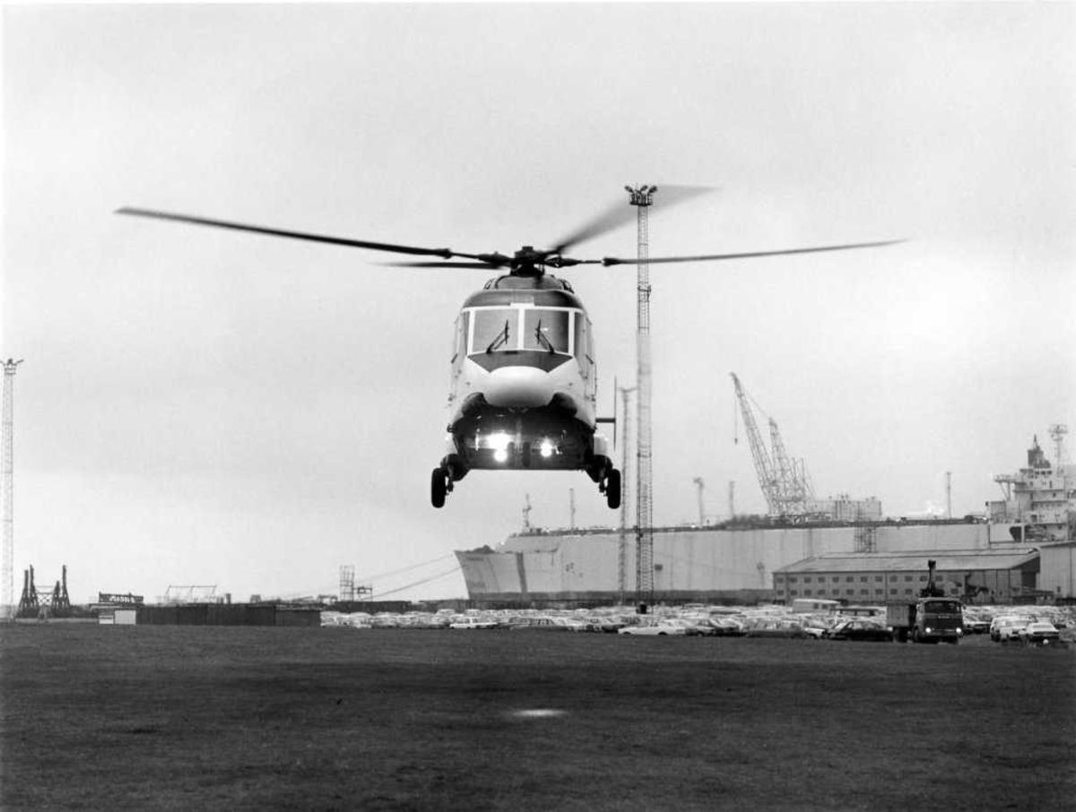 Ett helikopter i luften, Westland 30. Større skip i bakgrunn.