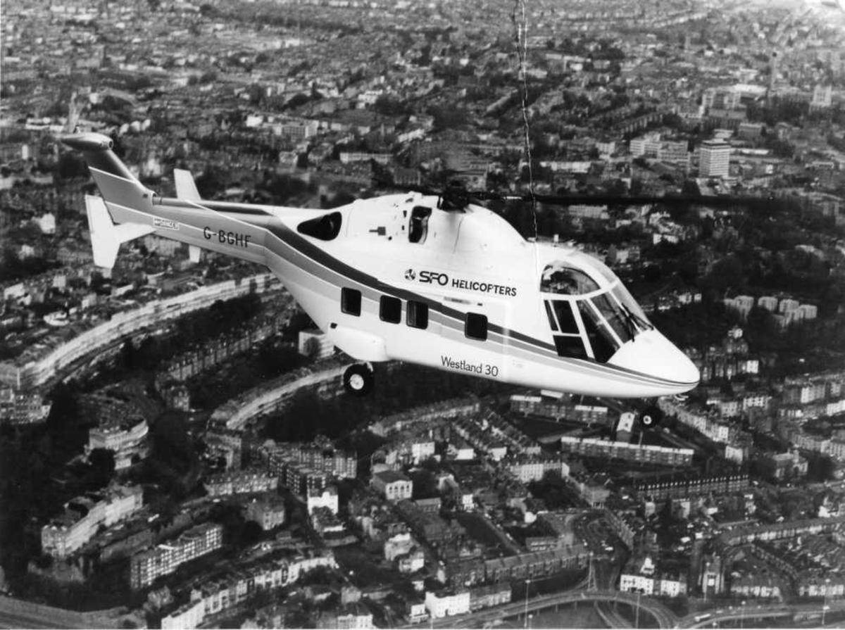 Ett helikopter i luften over by. Westland 30-100 G-BGHF i SFO Helicopters sine farger.