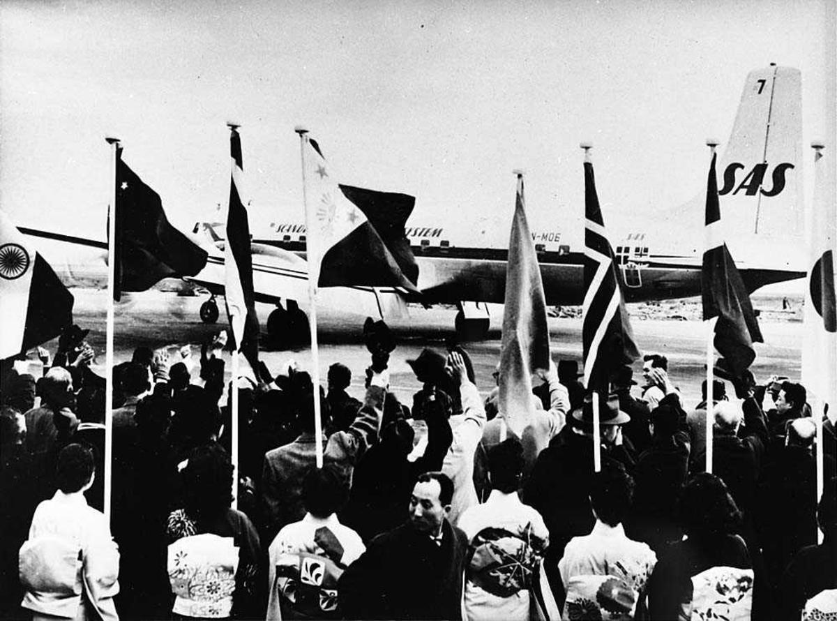 """Lufthavn. Folkemengde som står foran et fly på bakken, Douglas DC-7/C-74 Globemaster LN-MOE """"Reidar Viking"""" fra SAS. Flere flaggstenger blant folkemengden."""