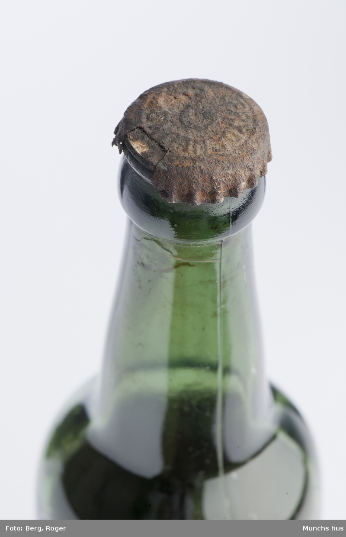 Ølflaske i grønt glass. Med kork. med innhold, antakelig øl. Tekst på kork: Frydenlund.