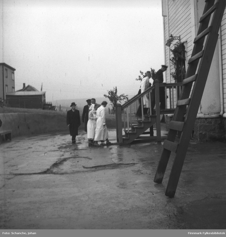 Kongebesøk:  Kong Haakon VII besøker sykehuset i Vadsø. Kongen går opp trappa til sykehuset med overlege Bjarne Skogsholm, oversøstre Anna Aase og resten av følget sitt. Byggning til venstre er huset til Thorleif Mathisen.