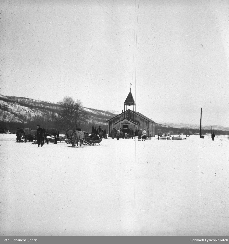 Polmak kirke fotografert på påsken -46. Utenfor kirken står hester med sleder. Folk er på veg til kirken. Bildet er tatt fra lang avstand.