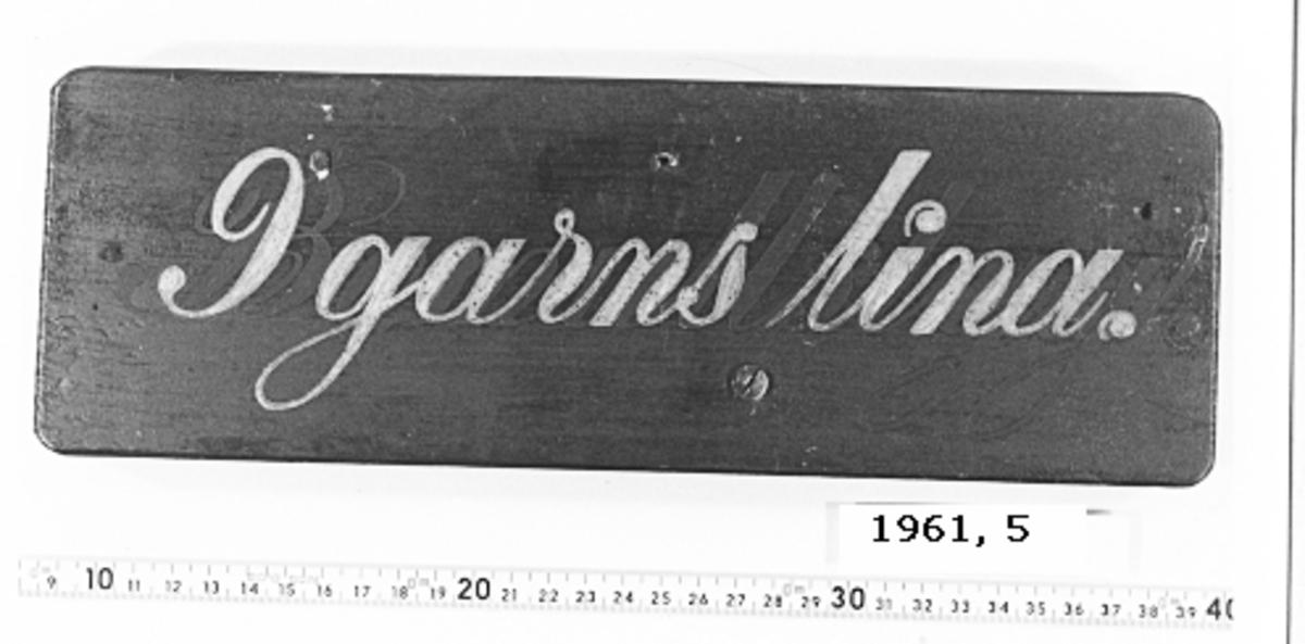 Skylt av trä, rektangulär och svartmålad med text i vitt.