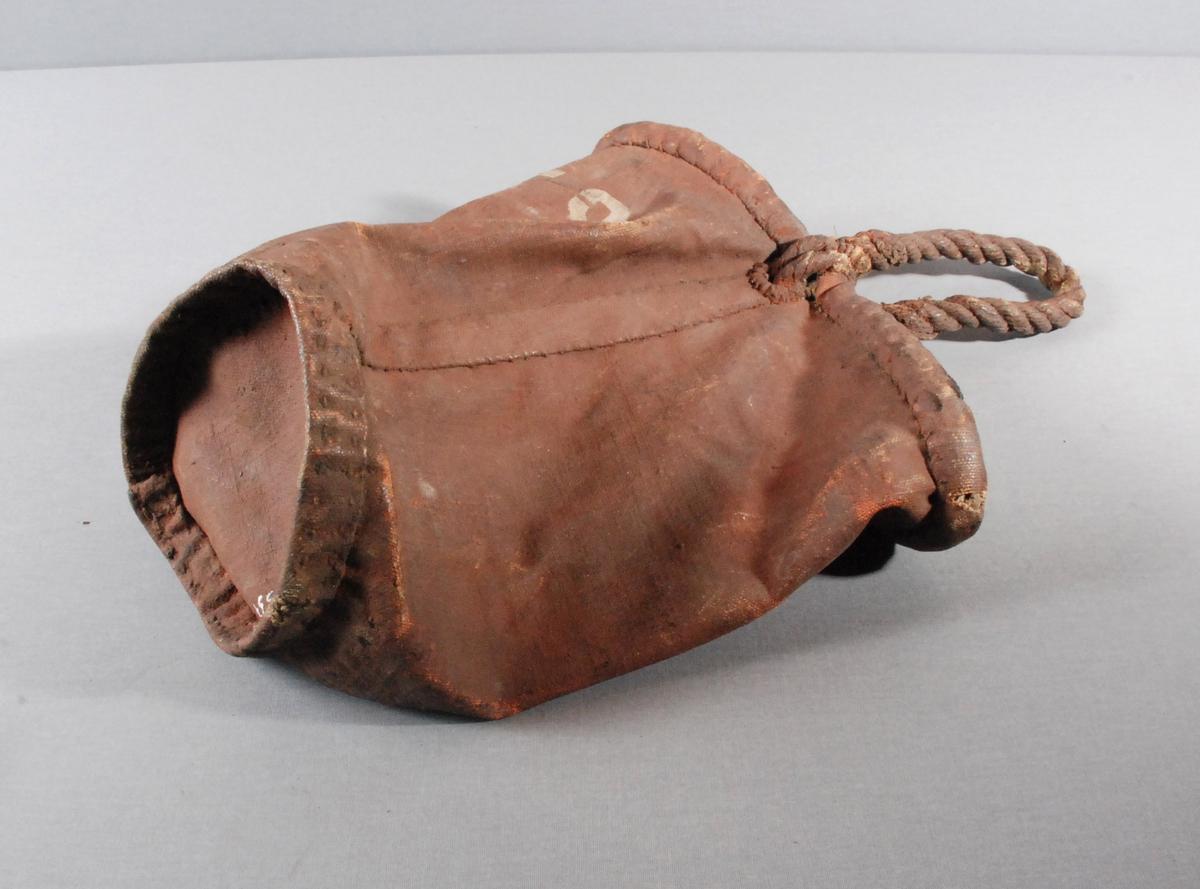 Brannbøtte i lerret, med kant undt øverste kanten av bøttent. Hanken er av tauverk som er tredd gjennom øverste kanten av bøtten.