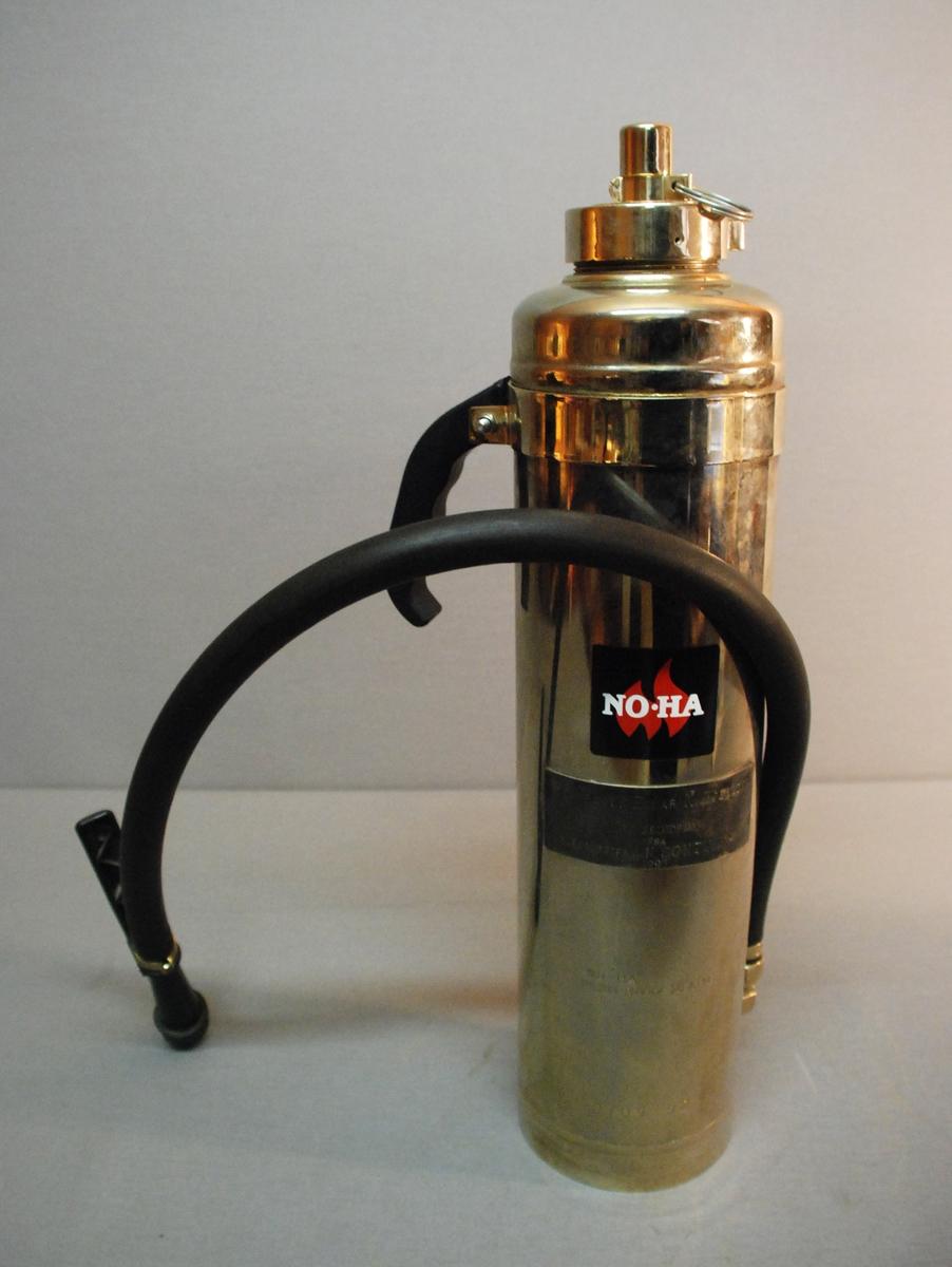 Håndslukker med sylindrisk kolbe med ventil på toppen og slangemunnstykke med håndtak.  Bærehåndtak festet øverst på apparatet. Slangen er festet i nedkant av apparatet.