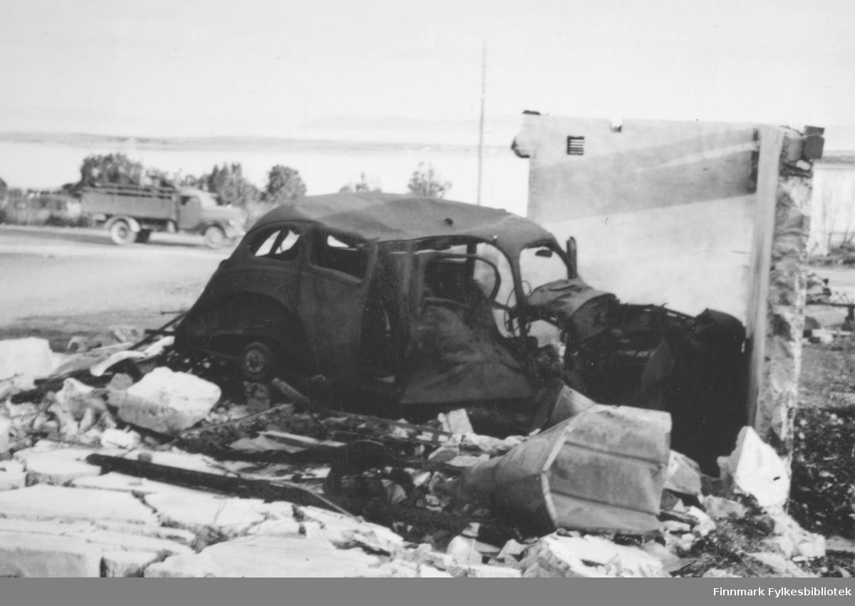 Forbrent bil liggende i ruiner i Vadsø sentrum etter andre verdenskrig. Deler av en hus- eller garasjevegg står inntil bilens front og side. I bakgrunnen ser man en vei, og en lastebil som kjører forbi i det bildet blir tatt. Bak der ser man trær, havet, en stolpe, og sannsynligvis en flik av Vadsøya. Bilen er trolig en firedørs amerikansk førkrigsbil.