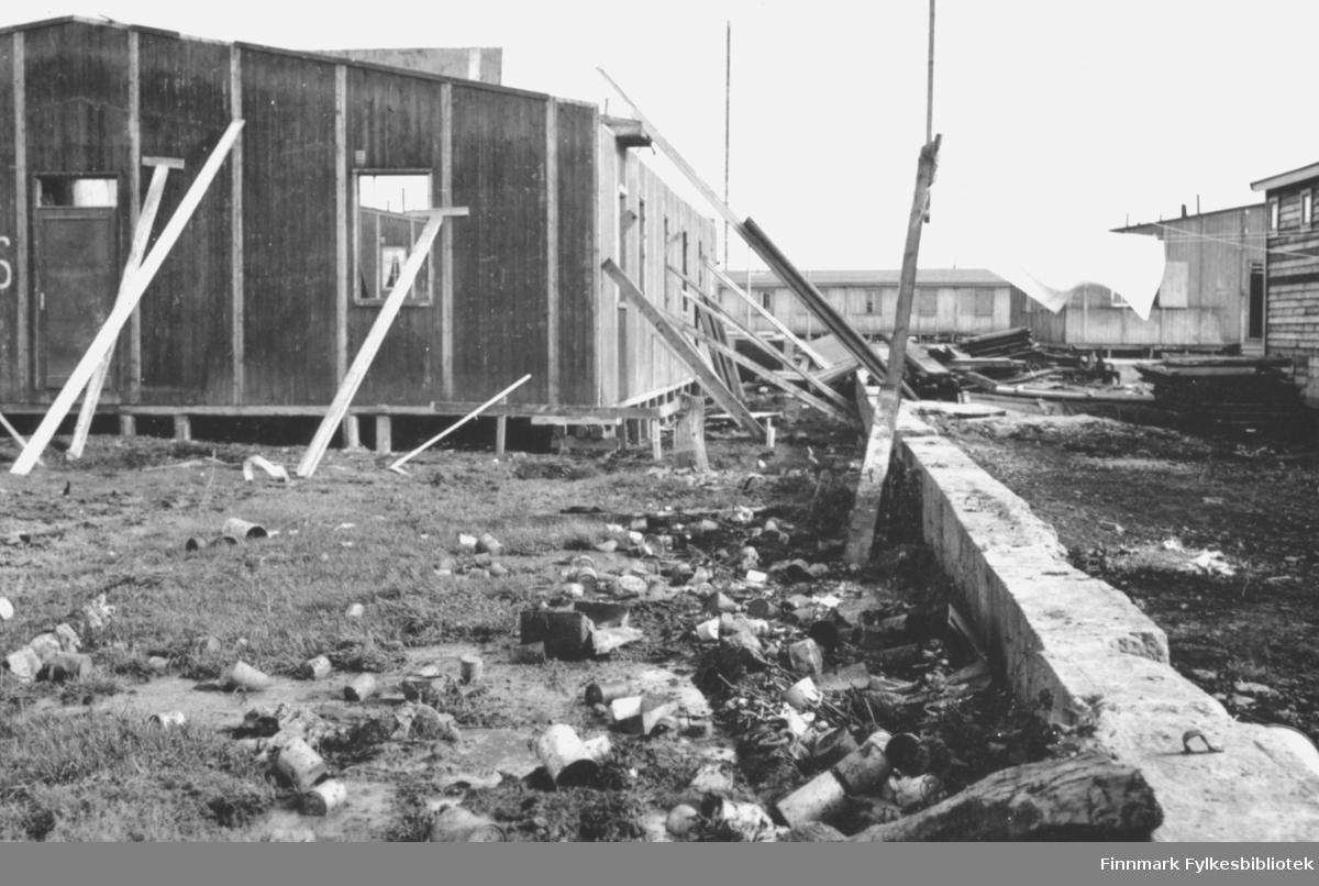 Brakke under bygging. Disse brakkene ble satt opp etter andre verdenskrig i Vadsø sentrum, for å huse de mange som hadde mistet hjemmene sine. Veggene blir støttet opp av planker. I bakgrunnen ser man flere ferdigbygde brakker. I forgunnen står en murkant. Klesvask er hengt opp fra en snor som er bundet i en planke som står støttet mot muren. Inntil muren ligger blant annet endel gamle bokser