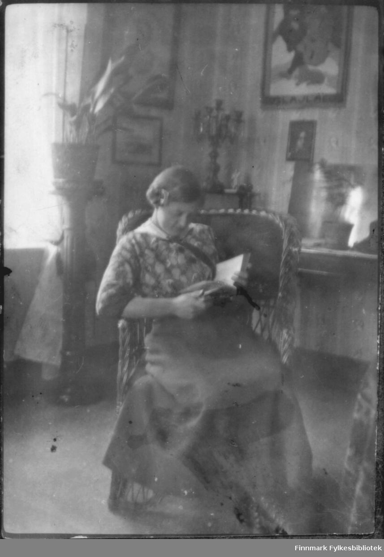 Kvinne leser i en bok. Interiør, antakelig Bergsfjord 1915-1920