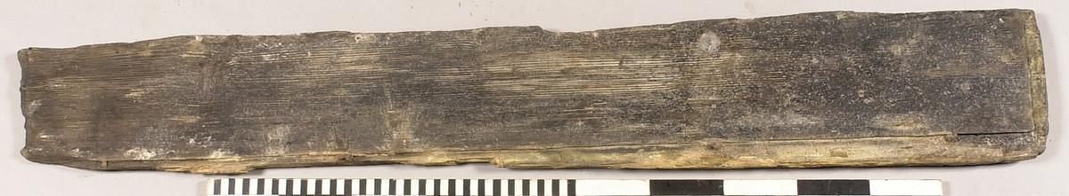 Del av en låda. Snedfasta urtag löper utmed kortsidorna samt ena långsidan. Ena änden är skadad. Fyra kvarsittande trädymlingar utmed ena långsidan.