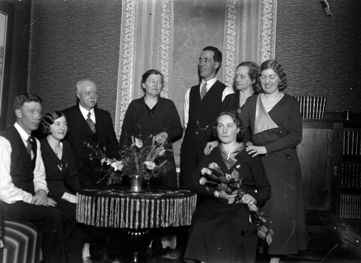 Människor är samlade runt ett bord. En kvinna har blommor i handen och på bordet står en vas med blommor.