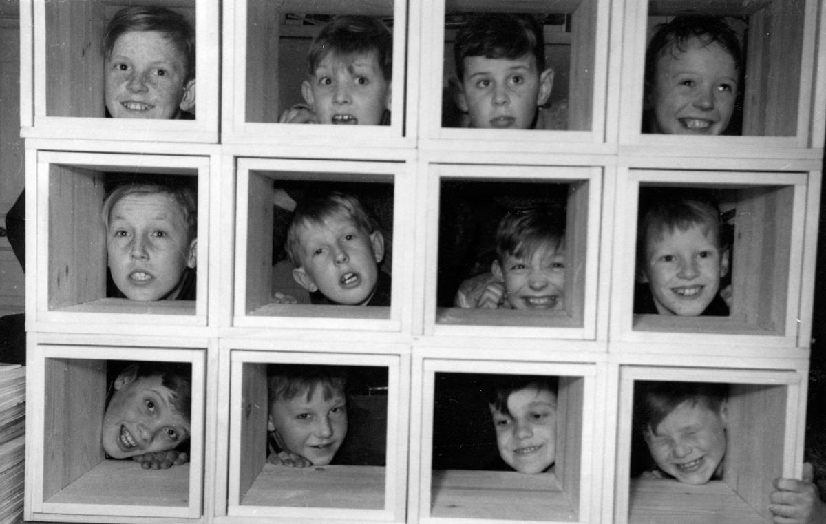 Pojkar tittar fram genom uppbyggda lådor på Vinterstugan i Jönköping. Det var bolaget som ägde huset och det fanns två tanter som höll vakt.