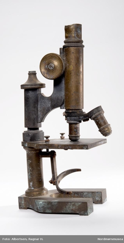 PROT: Et mikroskop funnet i branntomten på Høyere skoles trebygnings ruiner. Kjøpt til skolen i 1900 - det nyeste mokroskopet skolen hadde. (Prot.C.109).  Hesteskoformet sokkel.