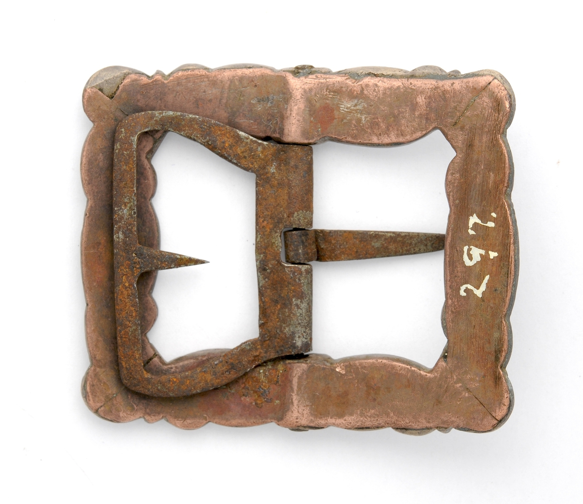 Spenne støypt i messing. Rektangulær form, litt bøygd. Stolpe, kalv og tann smidd i jern. Baksida forsterka med kopar.