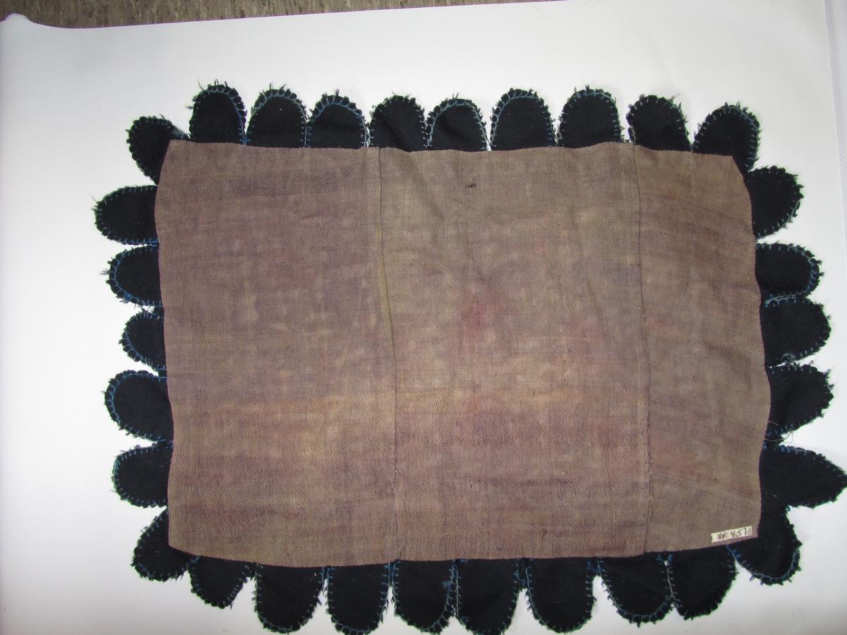 Teppe vevd i kypert, renning ufarga lin,innslag fiolett ull. Skjøytt saman av tre stykker. På denne botn er påsydd lappar i forskjellige fargar. Langs kanten to rader med mørkeblå tungeforma lappar,desse er kanta med lyseblå knappeholssting.