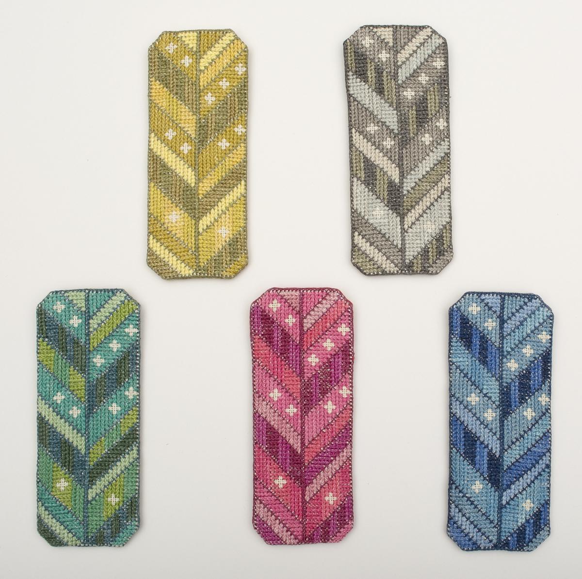 """Fem glasögonfodral, broderade med tvistsöm och korsstygn på linneväv på båda sidorna, fodrade med linne, infärgat i passande färg. Styvnad av """"skärpinläggnings-band"""". Motiv med lodrät rand, snett uppåtgående diagonaler från denna på båda sidor. Stjärnor framträder där linnebotten framträder d v s obroderade partier. Olika färgställningar: en rosa, en grön, en gul, en grå och en blå. Se också väska KLH.A7:694."""