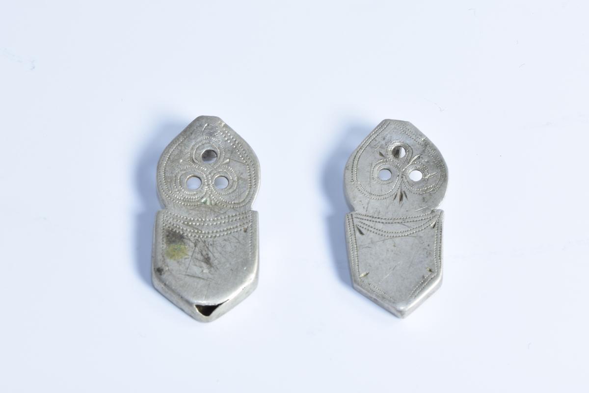 To sproter (beslag på den ene enden av belte til folkedrakt fra Setesdal) av sølv dekorert med siselerte border.