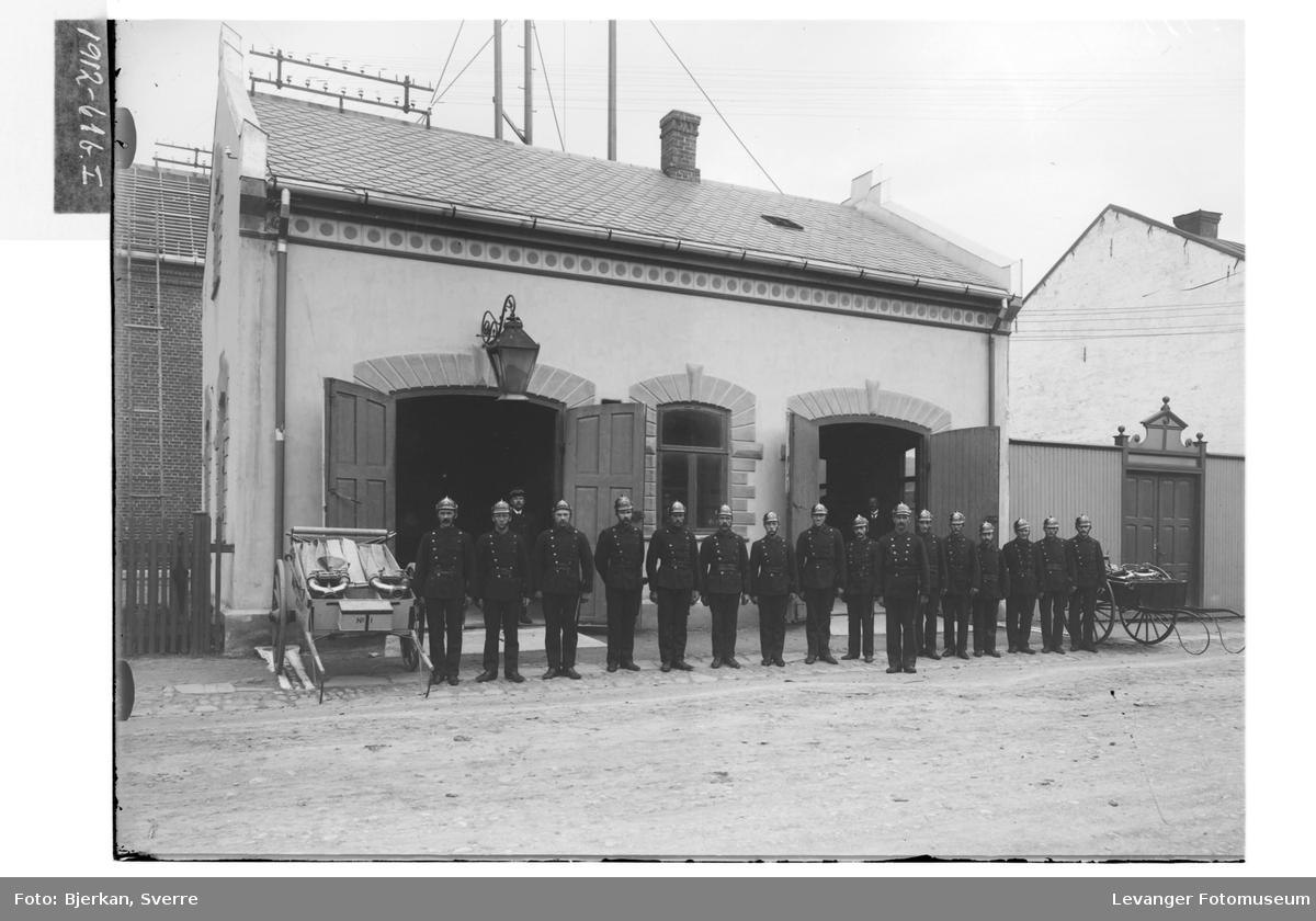 Brannmenn foran brannstasjonen.