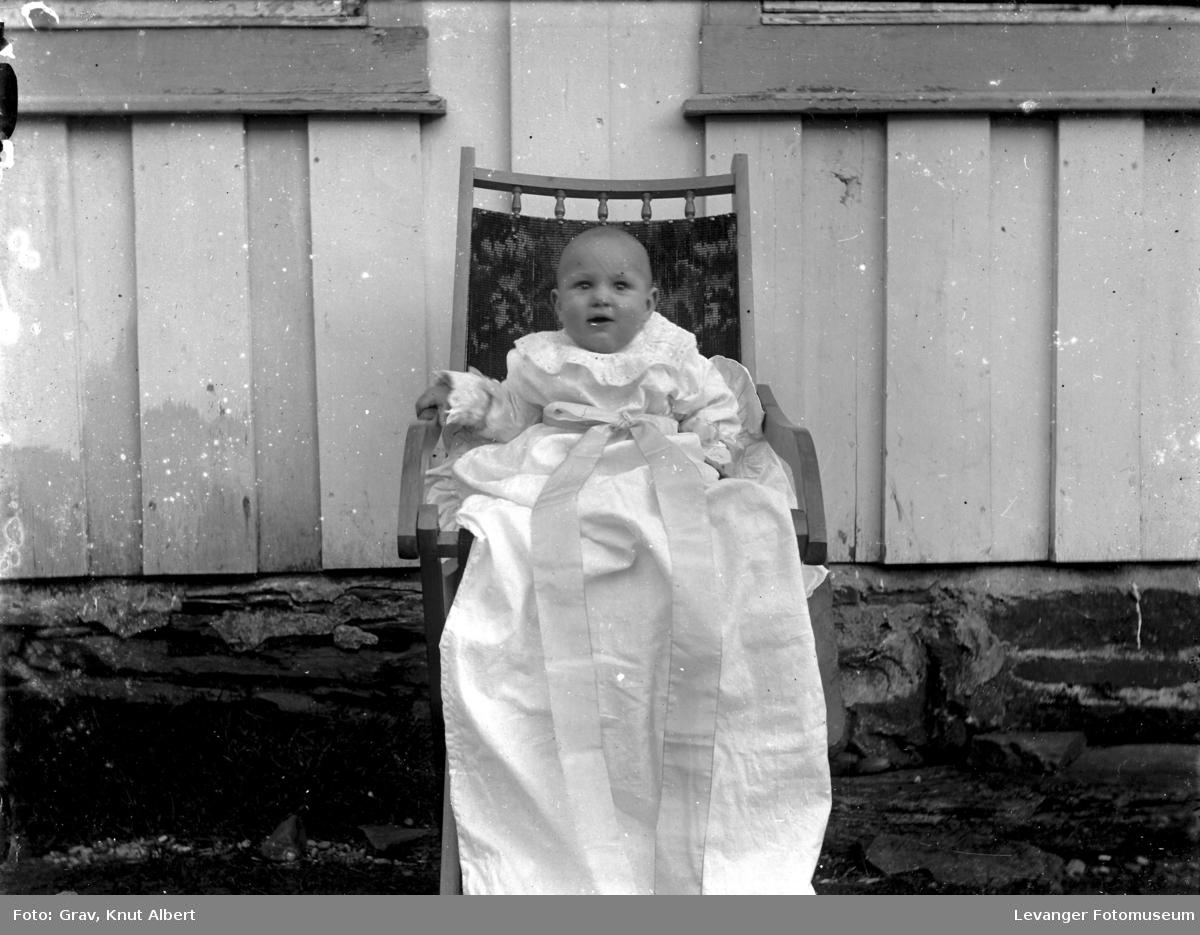 Barn i dåpskjole foran vegg ute.