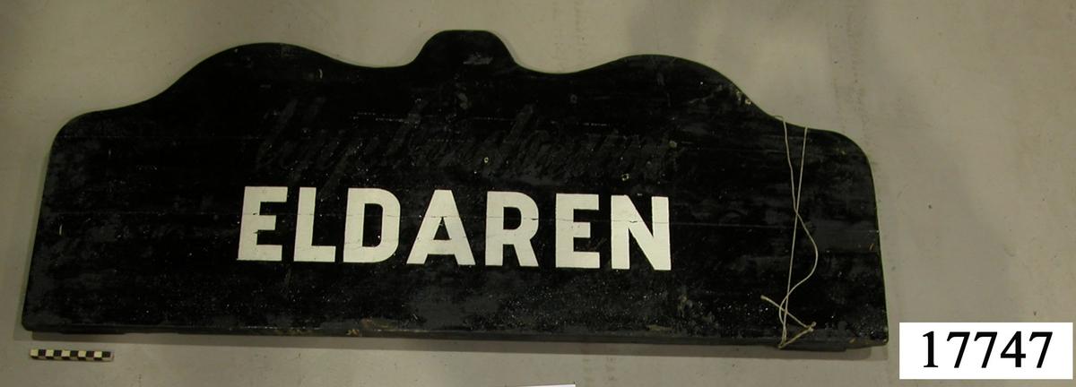 """Rektangulär skylt, ovansidan sågad i tre bågar, svartmålad. Vit schablonmålad text: """" ELDAREN """", övermålad text under svart färg: """" Uppbördsrum """"."""