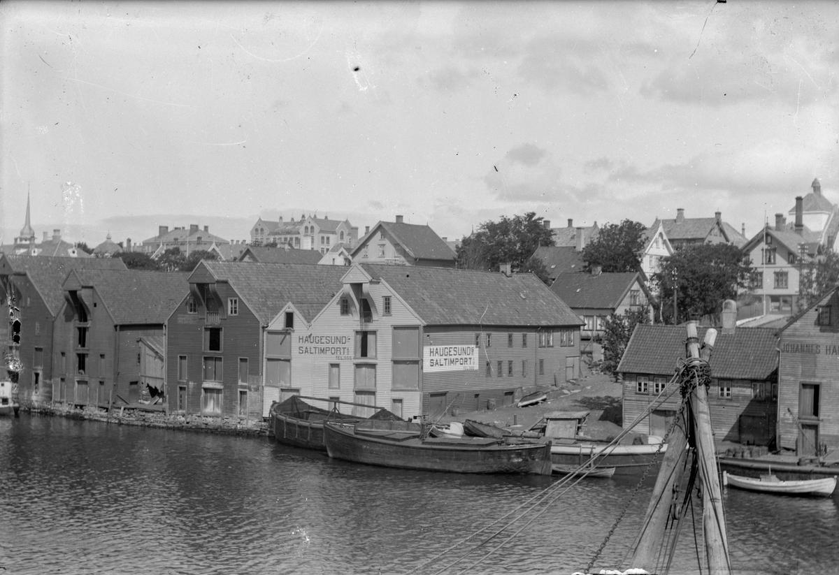 """Lektere ved kai sør i Smedasundet. I bakgrunnen til lhøyre taket på Festiviteten. Huset med spir til venstre er Strandgt. 92. I bakgrunnen ligger Breidablikk skole. To sjøhus på kaien som har påmalt skrift. Et med, """"Haugesund Saltimport"""" og et annet med  """"Johannes Haga"""". Treshusbebyggelse i bakgrunnen. Gaten på bildet er Knu Knutsen OAS gate, som tidligere het Banegaten."""