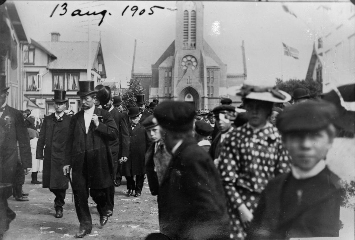 Torvet, utenfor Vår Frelsers kirke 13. august 1905. Flere personer. Kirken i bakgrunnen. Trehus til venstre. Norsk flagg i bakgrunnen til høyre.