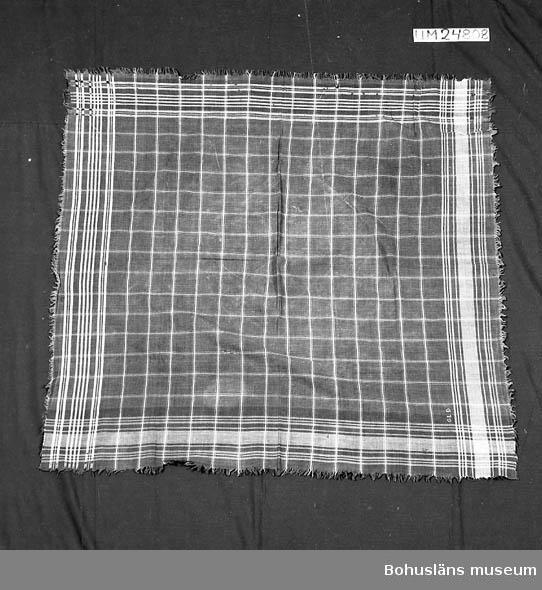 """Rutig tuskaftvävd schalett i blått och ljusblått. Huvudsakligen i bomull, men i bården längs två av sidorna finns ränder av beige silke (d.v.s. silketrådar både i varp och inslagsriktning). Bården längs de andra två sidorna har ljusblå ränder. Schaletten veks på diagonalen och sidan med silkeinslaget vändes utåt vid högtid. Andra sidan var vänd utåt till vardags. Det kallades """"söndagssida"""" och """"vardagssida"""". På vardagssidan är schaletten märkt med GLD broderat i korsstygn med beige silke. Fransar av varp och inslag. Ytterligare uppgifter om gåvan UM024798 – UM024 883, se UM024798. Två långa lagningar, gjorda med symaskin. Många småhål och bristningar.Något större hål mitt på. Fläckar och blekmärken. Fransarna slitna. Litteratur; Liby, Håkan, Folkligt dräktskick och folkdräktsrörelsen i Medelpad, Länsmuseet Murberget Härnösand Rapport nr 8 1984, Örnsköldsvik 1984, sid. 50-51.  Lychou, Kerstin, Hemslöjd och folkkonst i Bohuslän, Warne förlag AB, Partille 1996, sid. 123-129."""