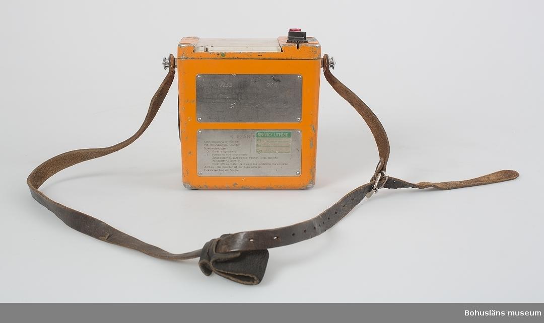 """Föremål  insamlade i projektet Oil Field Girls - petrokemisk industri i Stenungsund 2003-2004.  Gasmätare. Mätaren är till för att mäta halten syremolekyler i atmosfären.  Den används dels för att kontrollera att det finns tillräckligt med syre (luft) för att kunna andas vid inträde i utrymmen som varit slutna, ex, tankar kolonner och liknande. Men kanske vanligare var att mäta så att inget syre förekom i processutrustning där det måste vara syrefritt. Detta på grund av explosionsrisk och risk för oxidering (missfärgning avprodukten) som skall hanteras i utrustningen.  Text ur webbutställningen Kulturarv Stenungsund: """"Varje morgon kollar uteoperatören sin area, dvs. ett visst bestämt område på  fabriksområdet, med gastestaren så att det inte finns några gasläckor. Dessutom görs det kontroll med gastestaren inför förbokade arbeten som skall göras på fabriken till exempel innan svetsning.  Arbetena som skall göras har olika benämningar beroende på farlighetsgrad och man måste söka tillstånd för att få utföra arbetet. Olika blanketter för olika arbeten: het-arbete och kall-arbete.  Heta arbeten betyder att förekommer gnistbildning och att det därför är brandfarligt. Kallt arbete innebär ingen gnistbildning. För att få tillstånd till att utföra arbetet måste operatören sniffa med gastestaren för att skiftingenjören senare skall kunna godkänna att arbetet utförs.""""  Gassniffern ingår tillsammans med ögonduschar UM027903 - UM027904 och planimeter UM027917 i webbutställningens avsnitt Fabriksområdet som presenteras så här - ur intervju med operatör: """"Fabriksområdet kännetecknas av portar, stängsel och skyltar som bland annat förbjuder mobiltelefoner. Fabriksområdet är belyst nattetid. Facklan brinner alltid."""" Den som besöker en kemisk processindustri upptäcker snart  att den skiljer sig påtagligt från sådan tillverkningsindustri där råmaterial och produkter består av fast materia.  I de materialomvandlande processer som kännetecknar kemisk processindustri, ser man inte myck"""