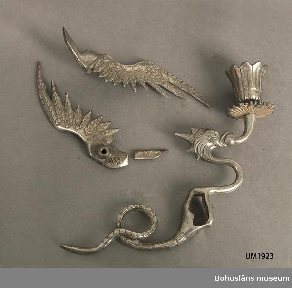 Ur handskrivna katalogen 1957-1958: Ljusstake i form av ett gripdjur L. c:a 20 cm. H. 16,5 cm. Av förnicklad, gjuten metall. Vingarna äro lösa. Hel för övrigt.  Lappkatalog: 90
