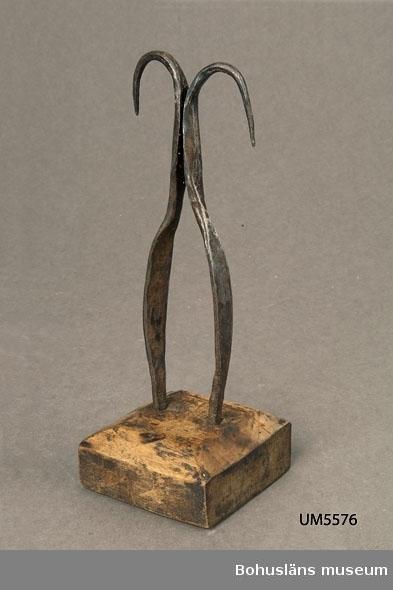 Ur handskrivna katalogen 1957-1958: Ljushållare Botten fyrsidig: 7,0 x 7,5. H: 21. Järn med träfot. Föremålet helt. Järnet rostat.  Lappkatalog: 90